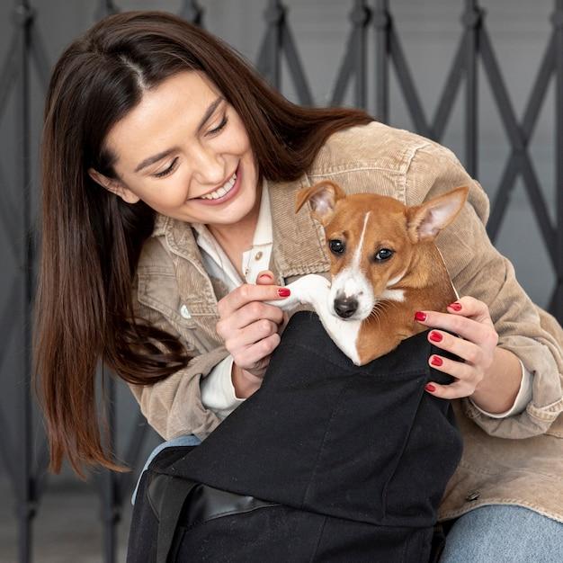 Женщина позирует со своей собакой и улыбается Бесплатные Фотографии
