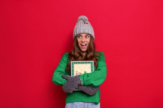 Женщина позирует в зимней шапке и перчатках с рождественским подарком Бесплатные Фотографии