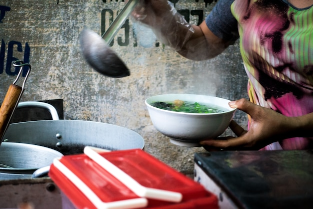 Woman pouring delicious vietnamese traditional pho soup in a bowl Free Photo