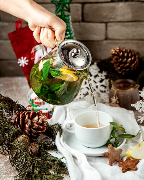 Woman pouring ginger tea with mint leave lemon and honey into cup Free Photo
