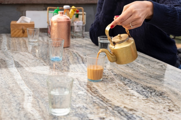 Woman pouring masala tea from teapot into cupglass on table in cafe. Premium Photo