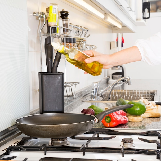 Woman pouring oil in the frying pan over the gas stove Free Photo