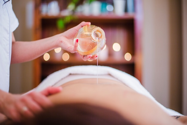 Женщина наливает масло на клиента Premium Фотографии