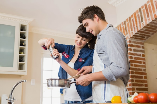 Woman pouring salt into utensil while man preparing a meal in kitchen Premium Photo