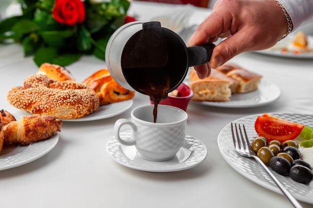 Женщина наливая турецкий кофе в взгляд со стороны кофейной чашки Бесплатные Фотографии
