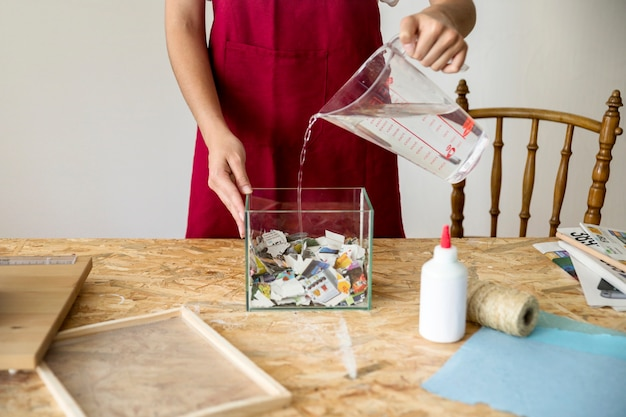 Woman pouring water in container filled with paper pieces at workshop Free Photo