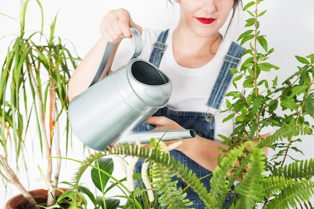 Woman pouring water on plants with watering can Free Photo