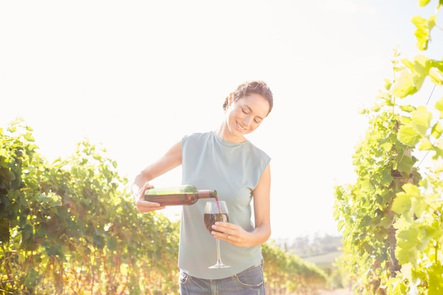 Woman pouring wine from bottle in glass on sunny day Premium Photo
