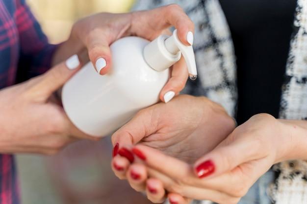 女性は屋外で友人の手に手指消毒剤を注ぐ Premium写真