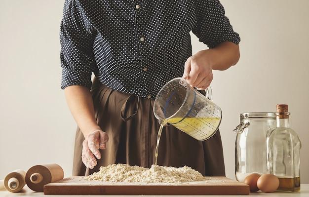 La donna versa acqua con olio d'oliva dal misurino alla farina a bordo, per preparare l'impasto per pasta o gnocchi. presentazione della guida alla cucina Foto Gratuite