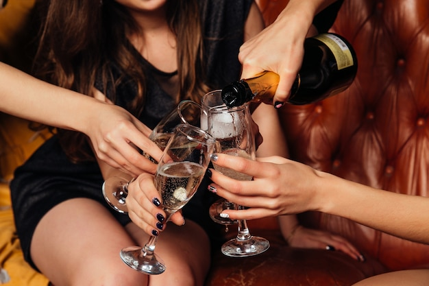 Woman pours white champagne into glasses. close-up Free Photo