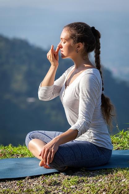 Woman practices pranayama in lotus pose outdoors Premium Photo