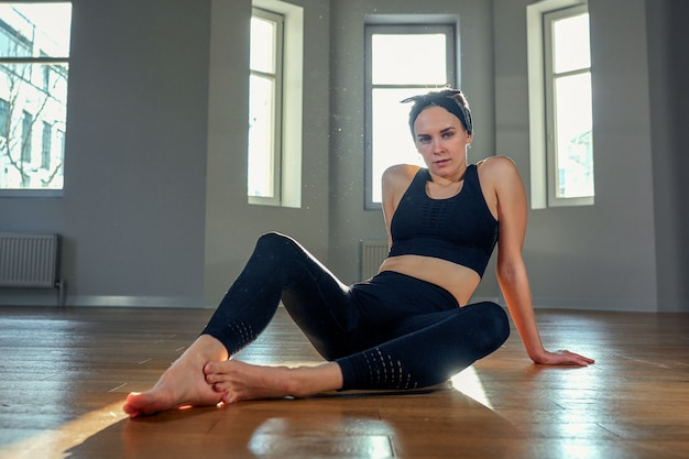 A woman practices yoga in a fitness room at dawn Premium Photo