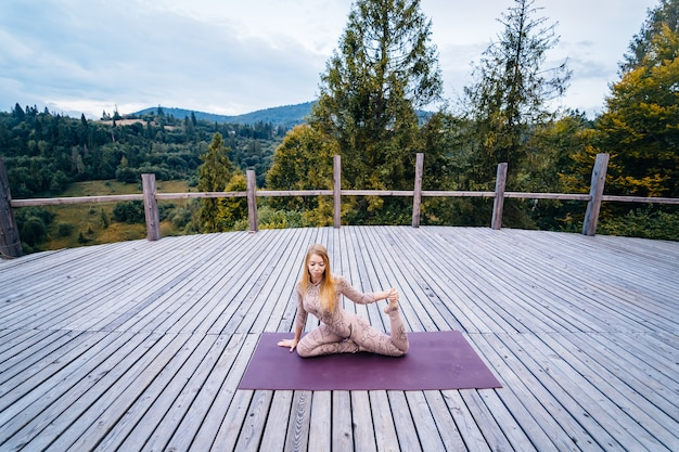 A woman practices yoga at the morning in a terrace on a fresh air. Free Photo