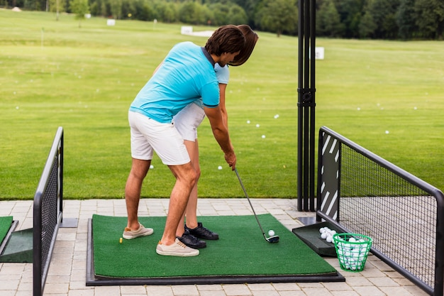 Woman practicing golf moves with trainer Free Photo