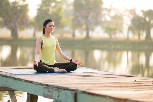 朝の公園でヨガをやってヨガを練習している女性 Premium写真