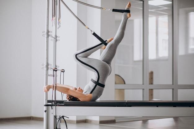 필라테스 개혁에 필 라 테 스를 연습하는 여자 무료 사진
