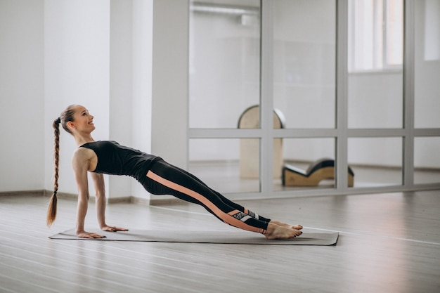 Woman practising yoga in the gym on a mat Free Photo