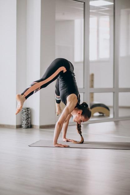 Woman practising yoga on a mat Free Photo
