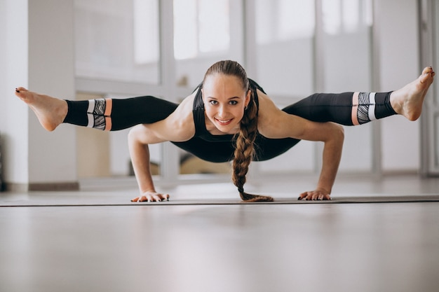 Woman practising yoga on a mat Free Photo