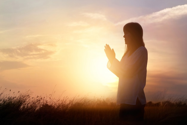 Woman praying and practicing meditating on nature sunset background, hope concept Premium Photo