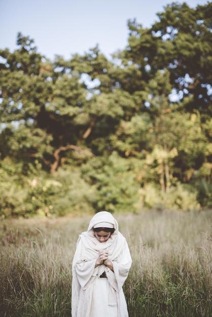 聖書のローブを着て祈る女性 無料写真