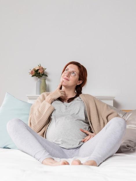 Женщина беременна дома в постели Бесплатные Фотографии