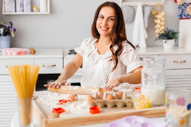 Woman preparing dough with kitchen roller Free Photo