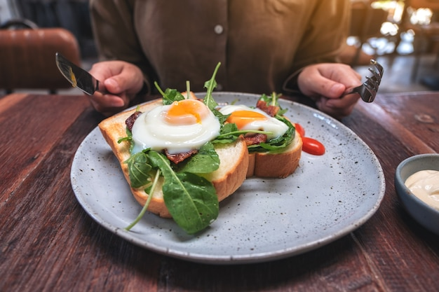 A woman preparing to eat breakfast sandwich with eggs, bacon and sour cream by knife and fork in a plate on wooden table Premium Photo