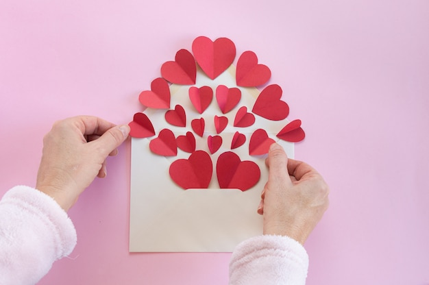 Woman preparing an envelope of hearts to send as congratulations on valentine's day Premium Photo