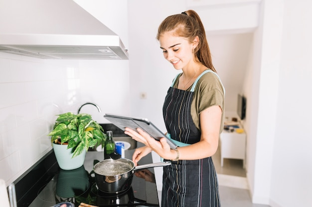 Woman preparing food by looking the recipe in the digital tablet Free Photo