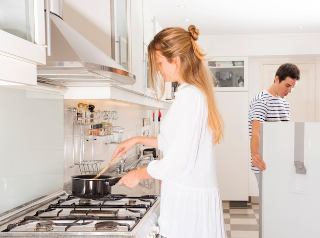 Woman preparing food while her husband looking in refrigerator Free Photo