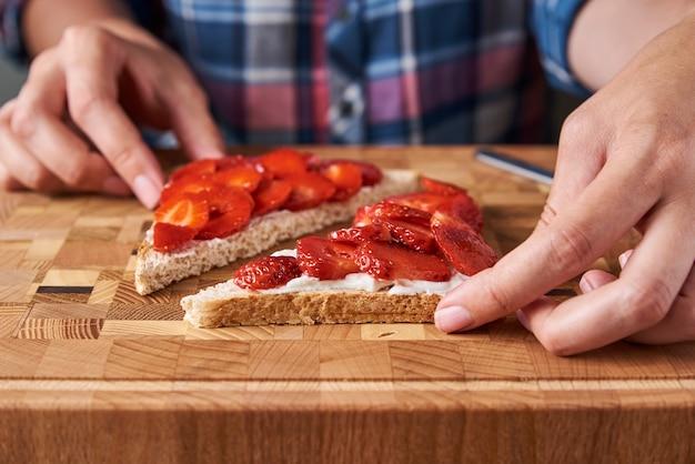 新鮮なベリーとサンドイッチを準備する女性 Premium写真