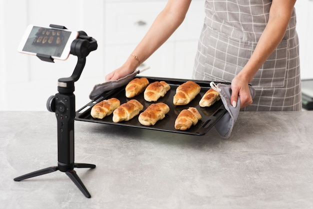 Woman presenting pastries on camera Free Photo