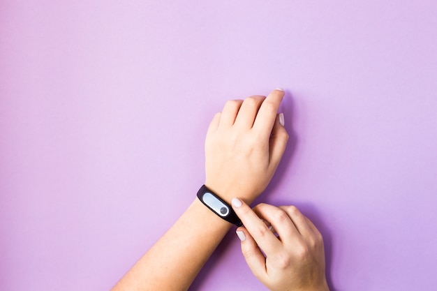 The woman presses the button of her fitness bracelet on her arm. on a bright purple background. healthy lifestyle and fitness concept Premium Photo