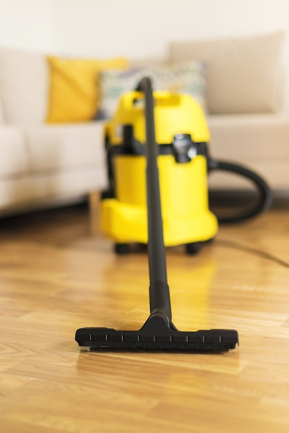Woman in protective gloves cleaning the living room with yellow vacuum cleaner. clean concept Premium Photo