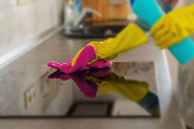 Woman in protective gloves wiping dust using cleaning spray and duster. cleaning service concept. Premium Photo