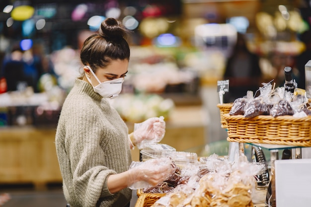 Woman in a protective mask in a supermarket Free Photo