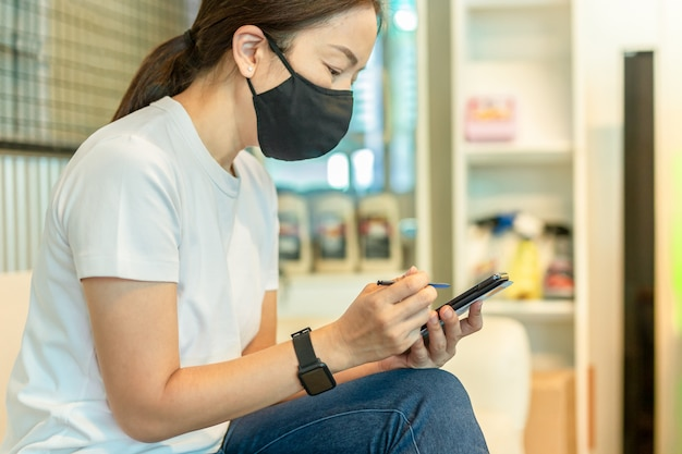 Woman in protective mask working on smart phone using digital pen. Premium Photo