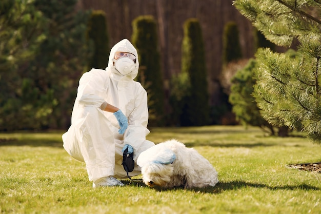 Woman in a protective suit walking with a dog Free Photo