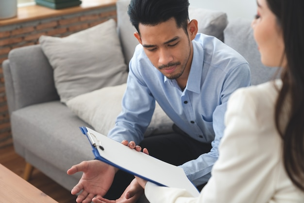 Woman psychiatrist talking with asian young man patient about his illness at hospital healthcare center Premium Photo