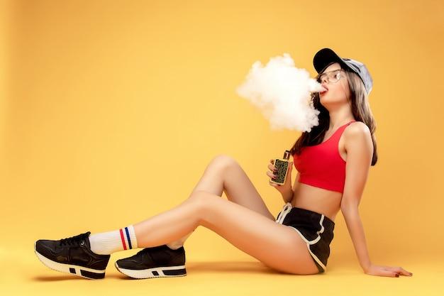 Woman puffing vapor on yellow Premium Photo