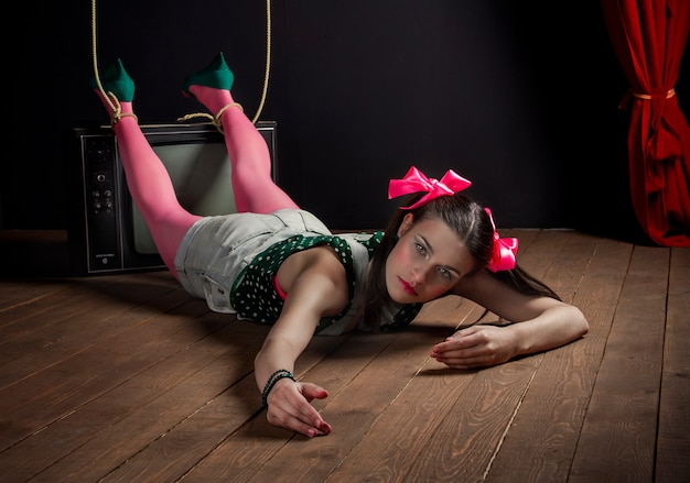 Woman puppet on tv with his hands tied posing Premium Photo