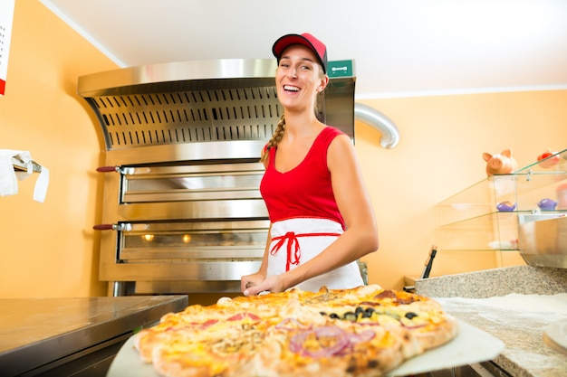 Woman pushing the finished pizza from the oven Premium Photo