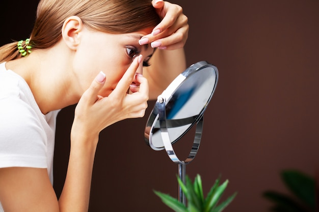 Woman puts on contact lenses for vision at home in front of a mirror Premium Photo