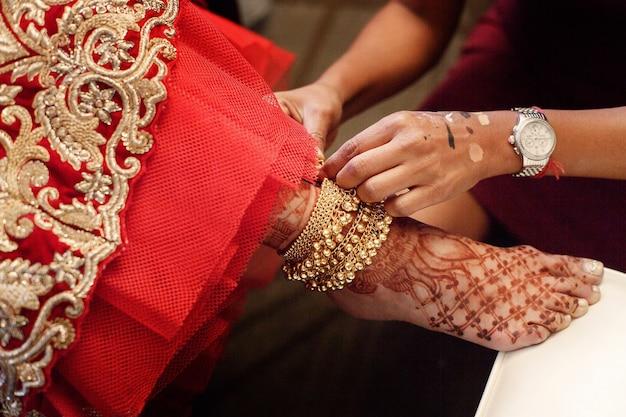 Woman puts golden bracelet with bells on bride's leg painted Free Photo