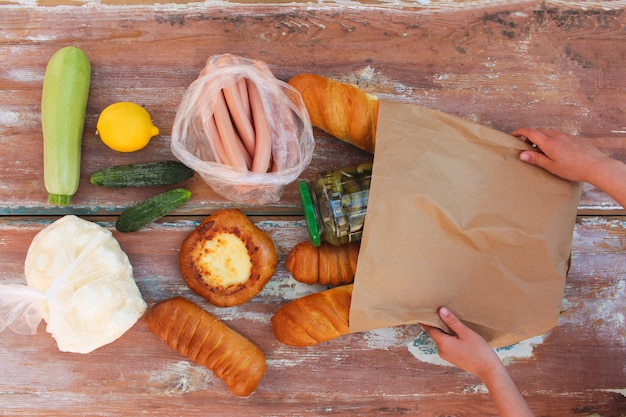 Woman puts purchase of paper bag on table in top view Premium Photo