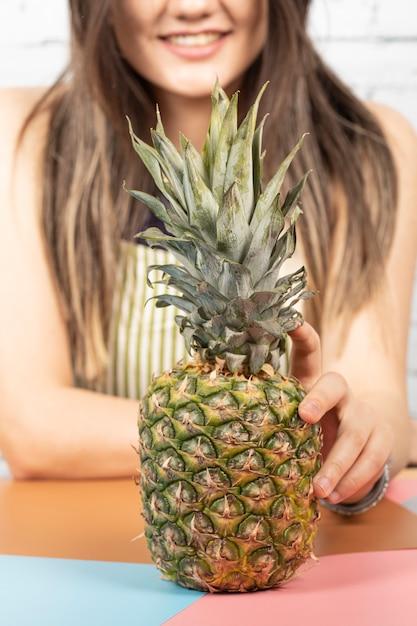 Женщина ставит ананас на стол Бесплатные Фотографии