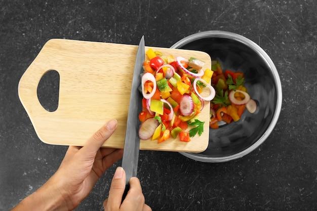 Женщина кладет нарезанный болгарский перец с луком в миску, вид сверху Premium Фотографии