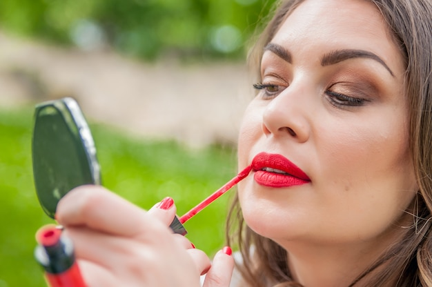 Woman putting, correcting red lipstick lip gloss. coffee shop restaurant urban outdoors background. mixt race model Free Photo